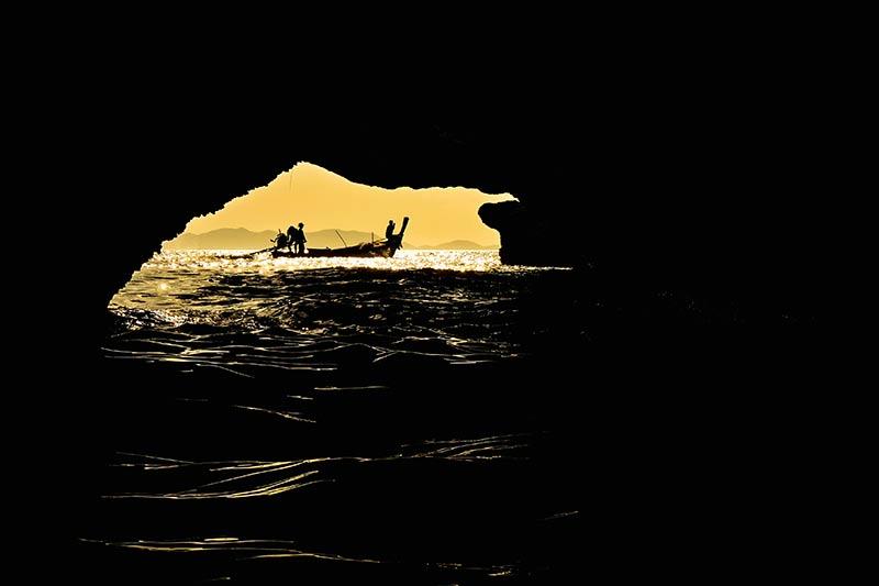 Opnieuwe en natuurlijk kader en het water op de voorgrond geven deze foto een mooie diepte bij het silhouet van de visser